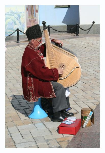 A guy in folk dress, playing a folk instrument, singing a folk song, and sitting on a bright blue plastic thing...  We thought he was cool.