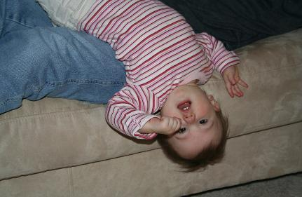 Hanging upside down from the couch.  It seems to me that Laura also has some pictures like this, too.